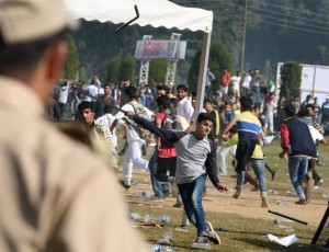 Srinagar: Youths throw stones and water bottles on police at the venue as violent clashes erupted during the first ever International Kashmir half-Marathon at Kashmir University Campus in Srinagar on Sunday. PTI Photo by S Irfan(PTI9_13_2015_000085A)